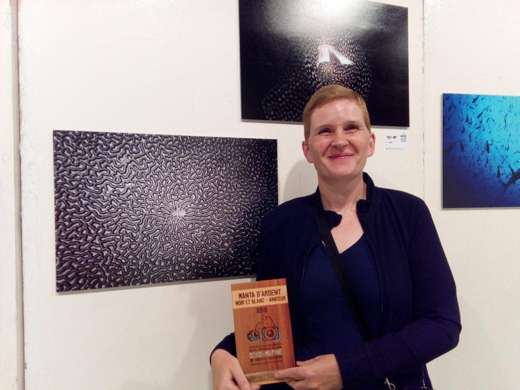 Moi devant ma photo au festival avec le prix en bois gravé que j'ai gagné